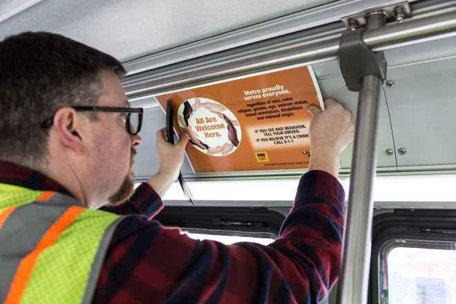 man placing placard inside bus