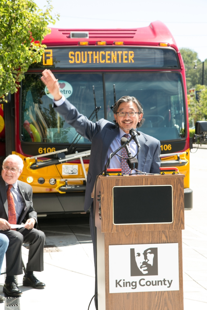 With a RapidRide F line bus in the background, Department of Transportation Director Harold Taniguchi waves.