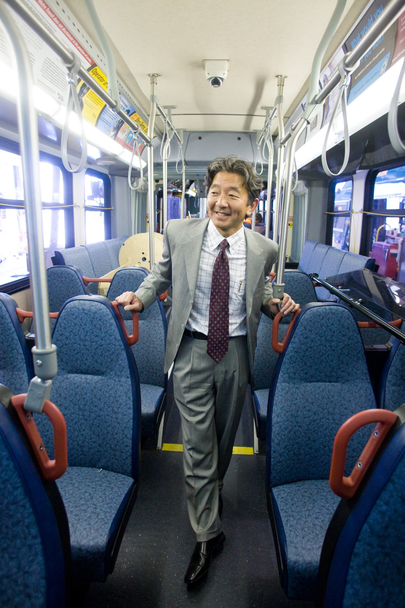 A photo of Department of Transportation Director Harold Taniguchi on a Metro bus.