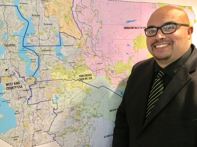 Hugo Garcia, King County Local Services' first Economic Development Program Manager, stands next to a map of King County.