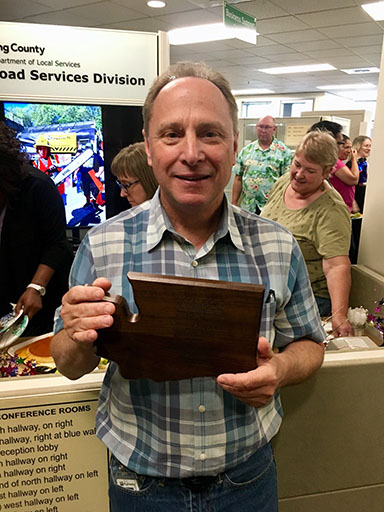 """Road Services Director Rick Brater holds his """"County Road Engineer of the Year"""" plaque."""