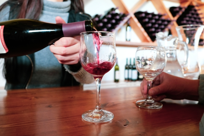 Pictured is a stock photograph of a someone pouring red wine into a glass at a tasting room.